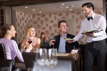 Waiter bringing delicious salads to visitors of restaurant