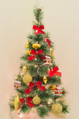 Traditional Christmas tree. Red and golden ornaments and lights on a fake fir tree. Create a festive xmas mood at home.