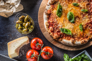 Italian traditional pizza margarita on round wooden board with basil tomatoes and parmesan