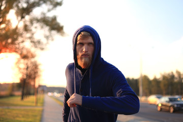 Fit athlete. Handsome adult man running outdoors to stay healthy, at sunset or sunrise. Runner.