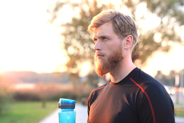 Handsome adult man drinking water from fitness bottle while standing outside, at sunset or sunrise. Runner.
