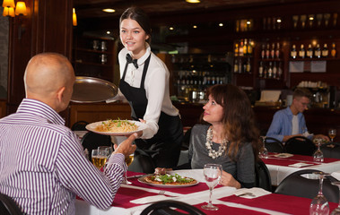 Young waitress bringing spaghetti to couple