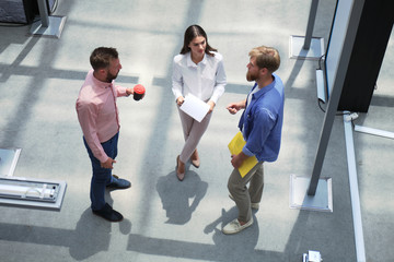 Top view of young modern people in smart casual wear discussing business while standing in creative office.