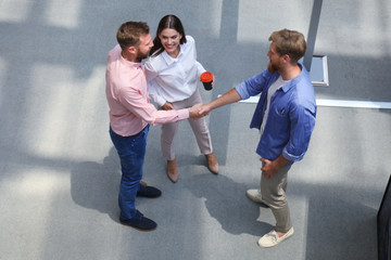 Top view of young modern people in smart casual wear shaking hands standing with their colleagues in creative office.