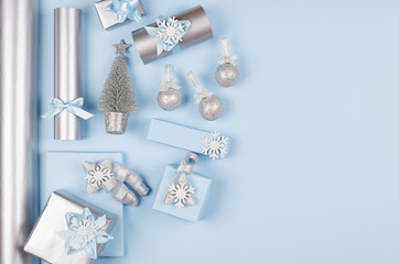 Modern soft minimalist christmas background with copy space - pastel blue and silver metallic gift boxes with shiny ribbons and bows on blue color backdrop, top view.