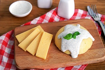 Polenta or hominy, a dish of corn grits or corn flour on a brown background. Served with sour cream and mint sauce.