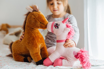 Little girl playing with soft toys
