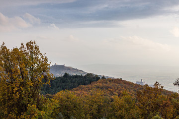Beautiful view of Assisi town (Umbria) in autumn from an unusual place, behind an hill with orange, yellow and green trees