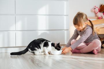 Little girl feeding cat