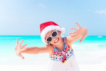 Adorable little girl in Santa hat during Christmas beach vacation