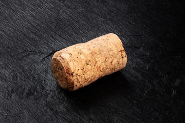 A closeup photo of a champagne cork on a black background with a place for text