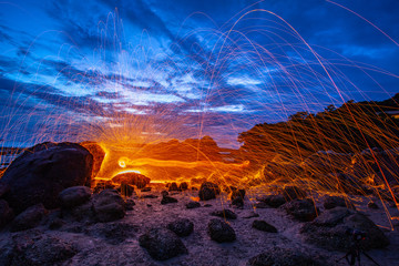 cool burning steel wool fire work photo experiments on the rock at sunrise..