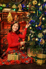 Beautiful happy little girl at home by Christmas tree
