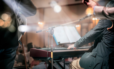Shot of a man playing piano on stage in live concert of electronic music