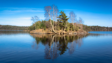 A small island which is reflected in a local lake sweden gothenburg