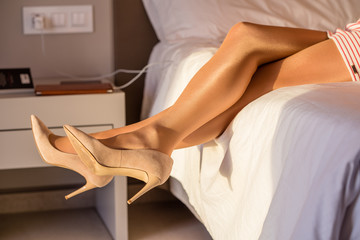 woman sitting on the bed in high heels