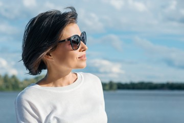 Portrait of mature woman in profile in sunglasses resting on the nature near the river