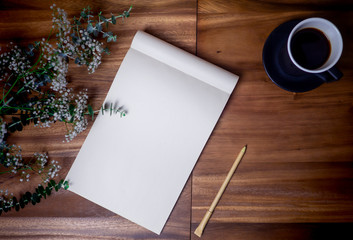 Flat lay of blank white notebook with cup coffee on wooden table. Copy space. ready for adding text or mockup.