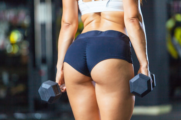 Athletic buttocks of fit girl wearing sporty shorts with dumbbells in gym back view