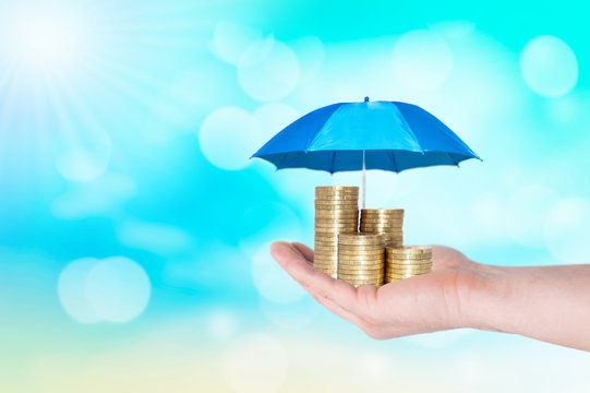 Umbrella protection coins hand man holding stack of money savings a business. Protection money concept