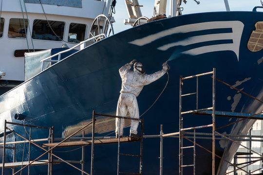 pintor pintando el casco de un barco , el pintor está protegido con una máscara y un buzo blanco y está trabajando sobre un andamio