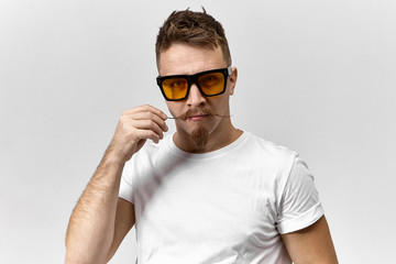 Portrait of funny handsome young European male wearing white t-shirt and rectangular yellow tinted eyeglasses while working in front of computer screen, curling his stylish mustache using hair wax