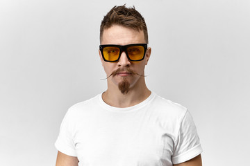 Style, fashion and optics concept. Portrait of handsome fashionable young Caucasian male posing in studio wearing white t-shirt and yellow rectangular eyeglasses, having serious confident look