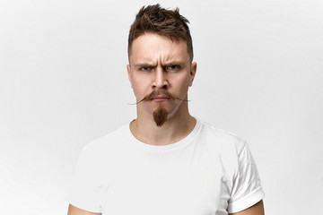 Negativity, bad mood and emotions concept. Portrait of grumpy offended bearded male with funny hipster mustache staring at camera with angry look, frowning, dissatisfied with annoying noise