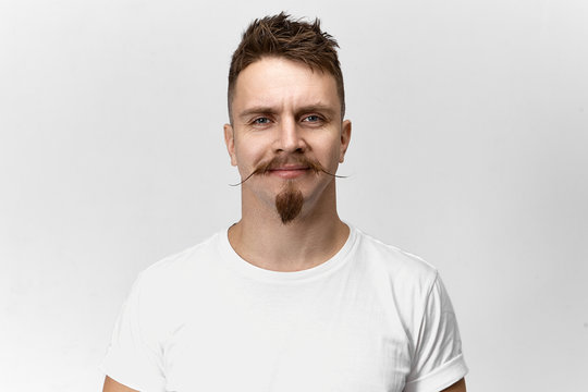 People, style, hairdressing and fashion concept. Isolated shot of happy cheerful young European hipster guy smiling, rejoicing at his news stylish haircut, mustache and beard at barbershop