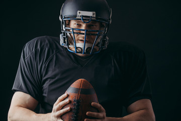 People, achievement and sport concept. Athletic american football player in black helmet and jersey posing with a ball isolated on black background