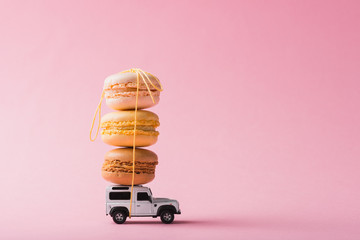 Aluminium Prints Macarons Macaron cookies on top of a toy car over pink background