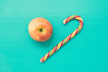 Apple and candy cane on turquoise wooden background, top view. Filter effect