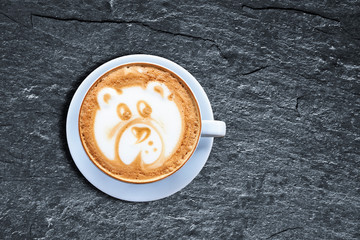 Teddy bear latte art coffee cup on textured black shist with oblique light