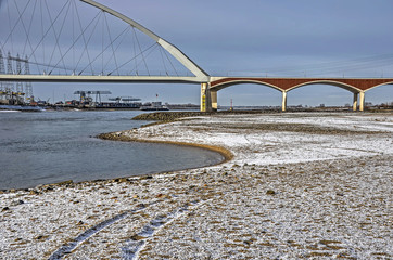 Snow covered river beaches make curves in the landscape of the floodplain of the river Waal near city bridge De Oversteek (The Crossing) in Nijmegen, The Netherlands