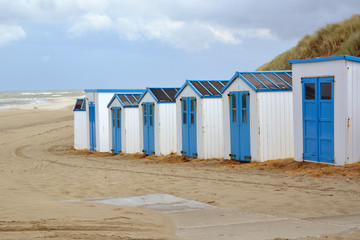 Row of white and blue beach sheds on the beach of Texel in the Netherlands