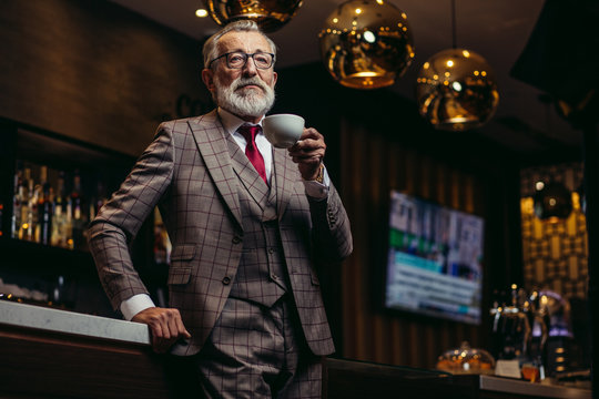 Portrait of wealthy prosperious senior businessman in drinking coffee near bar counter at elite gentlemen club