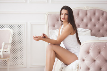 Portrait of young beautiful woman in the bedroom. Attractive woman indoors.  Girl sitting on the bed.