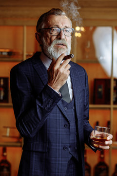 Successful old-aged european businessman spending night in luxury restaurant, smoking cigar and drinking alcohol beverages, looking at camera over bar counter background.