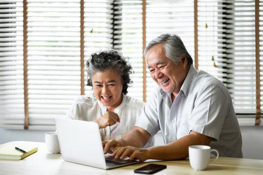 Relaxing Asian Senior Couple having fun with laptop computer.