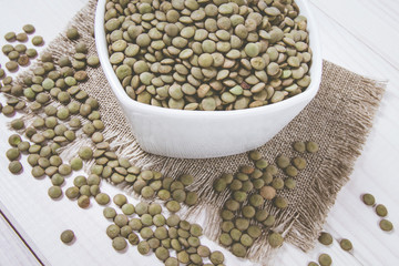 Green lentils in a bowl on a wooden background.