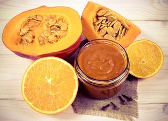 Homemade preserves. Pumpkin jam on a wooden background.