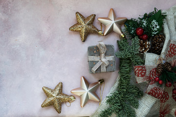 Golden stars, gift box, christmas tree branch and decorations on light pink textured background. Christmas, new year, winter concept. Flat lay, top view, copy space