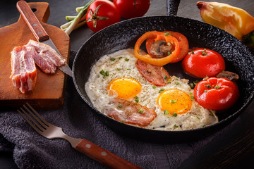 Fried eggs with bacon and tomatoes on an old cast iron pan and cutlery on a gray table. Close-up
