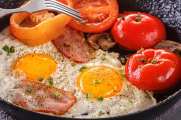 Fried eggs with bacon and tomatoes in an old cast-iron pan. Close-up