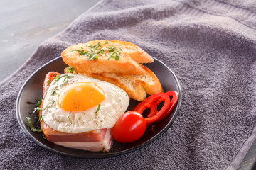 Fried egg with bacon in a black plate with fried pieces of bread, greens and tomatoes on a gray wooden table. Close-up. Copy space