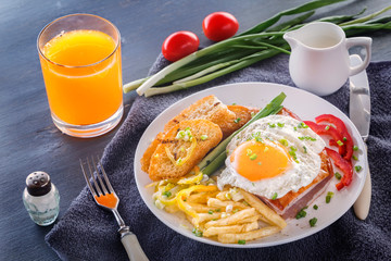 Fried egg with bacon in a white plate with fried pieces of bread, greens, tomatoes, french fries and a glass of fresh juice on a gray wooden table. Close-up