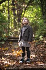 Autumn girl / Adorable little girl is walking through an autumn forest