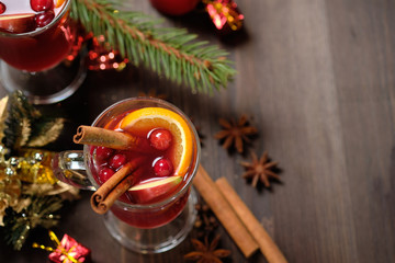 Mulled wine on a wooden background with candles, pine branches and Christmas lights. Selective focus.  Copy space