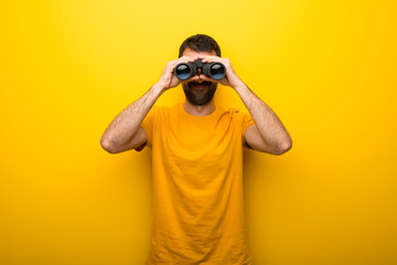 Man on isolated vibrant yellow color and looking for something in the distance with binoculars