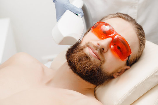 Young man demonstrates smoothness of skin with laser hair removal on face and body. Close up